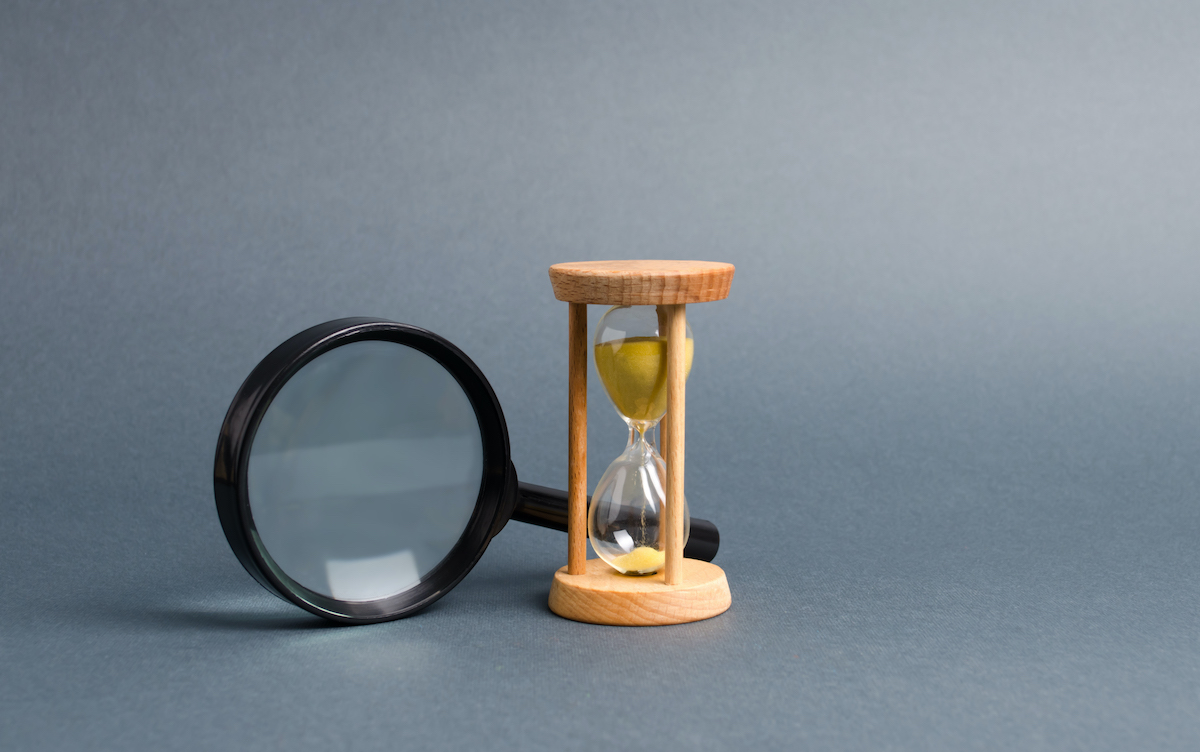 Magnifying glass and hourglass. Search for time and resources. Streamline business, increase efficiency and reduce downtime. Find in the shortest possible time. Effective business solutions